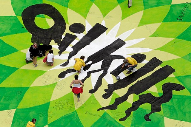 Greenpeace activists paint over a banner with the British Petroleum logo in a protest against the BP oil spill in the Gulf of Mexico in Vienna